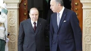 France's Foreign Minister Laurent Fabius (L) and Algeria's President Abdelaziz Bouteflika