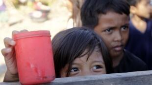 Des enfants dans l'attente de distribution de denrées alimentaires après le passage du typhon Bopha qui a dévasté le sud des Philippines.