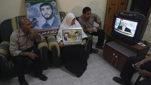 The family of a Palestinian prisoner watches Hamas chief Khaled Meshaal's address on TV in Gaza