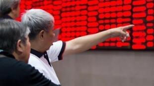 Des investisseurs dans une salle boursière montrant des informations sur les cours des matières premières à Nanjing dans la province du Jiangsu, le 23 octobre 2015.