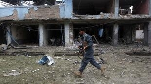 An Afghani police officer at the scene of the bomb attack in Jalalabad on August 3, 2013