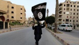 Um jihadista do grupo Estado Islâmico com uma bandeira do grupo, na cidade de Racca, na Síria.