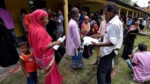 Moradora de povoado do estado de Assan mostra seus documentos para o agente do censo, em agosto de 2018.
