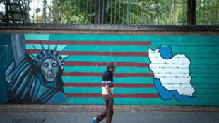 Homem passa diante de campanha contra os Estados Unidos pintada em muro nas ruas de Terrã