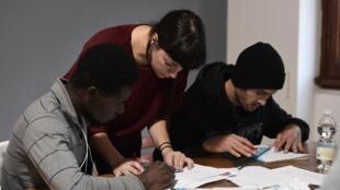Une bénévole aide des migrants à étudier pendant un cours, dans le cadre d'un programme d'aide à l'intégration des migrants, en Italie.