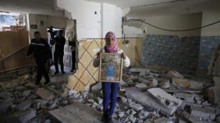 Familiar mostra o retrato de Abdelrahmane Shalodi nos meio dos destroços da casa do palestino destruída pelo exército israelense na madrugada desta quarta-feira (19).