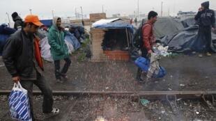Des migrants quittent leur camp à Calais où ils étaient  installés depuis des semaines dans l'espoir de rejoindre l'Angleterre.