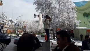 دختر جوانی در خیابان انقلاب تهران علیه حجاب اجباری اعتراض میکند
