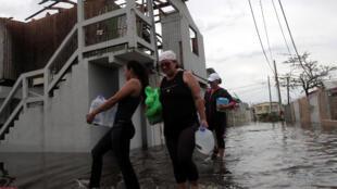 Ciudadanos de Catano, al suroeste de San Juan, transportan víveres después del paso del huracán María el 21 de septiembre de 2017.