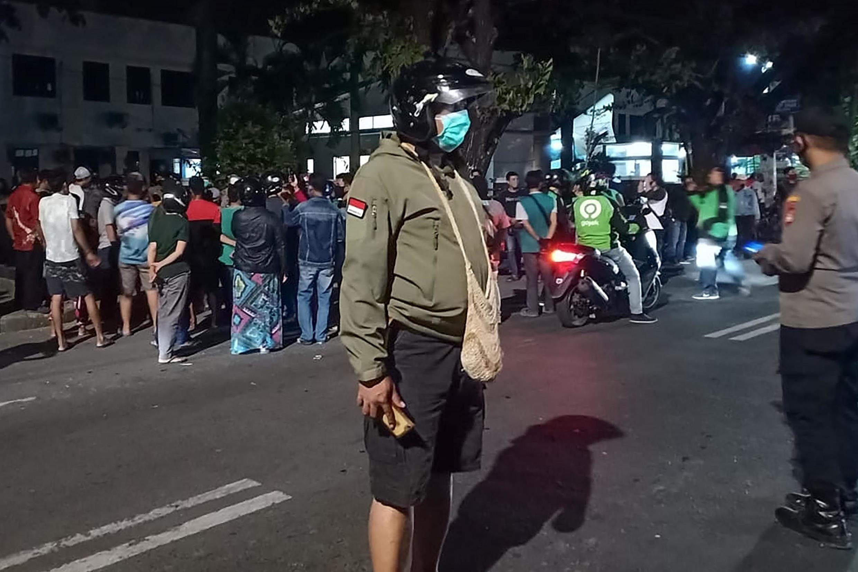 Des policiers indonésiens sécurisent la morgue de l'hôpital Stella Maris à Makassar, à Sulawesi Sud, face à la foule désireuse de récupérer les dépouilles de leurs parents sans respecter le protocole contre le coronavirus.