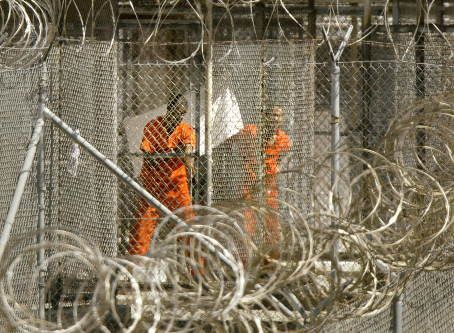 In this file photo taken on January 27, 2002, a detainee from Afghanistan cleans himself as another detainee looks out from his enclosure at the US naval base in Guantanamo Bay, Cuba