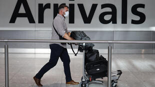 Un pasajero con mascarilla por precaución ante el coronavirus llega al aeropuerto de Heathrow, el 22 de mayo de 2020 al oeste de Londres