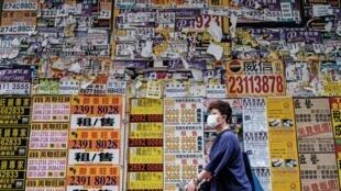 Una persona pasa por delante de una tienda cerrada de Hong Kong cubierta de anuncios el 20 de julio de 2020