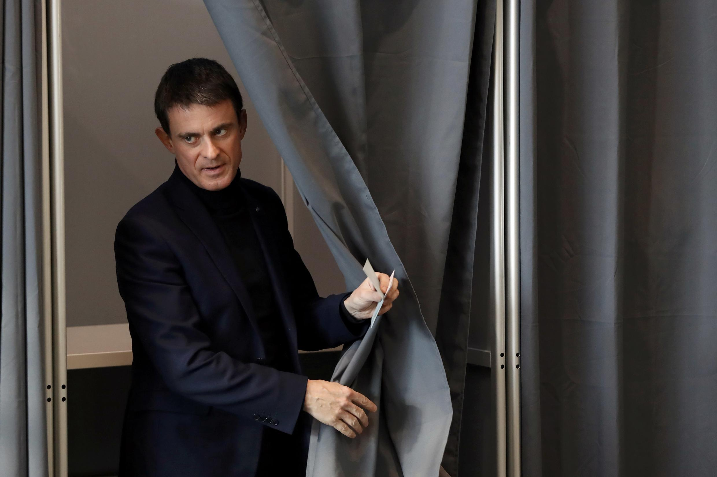 Former French Prime Minister and candidate Manuel Valls holds his ballot as he votes in the first round of the French left's presidential primary election in Evry, France, January 22, 2017.