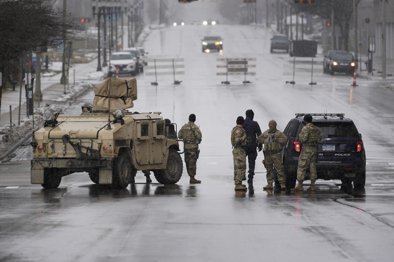 La Guardia Nacional de Michigan y la policía de Lansing patrullan en las afueras del capitolio estatal en Lansing, Mich., el domingo 17 de enero de 2021.