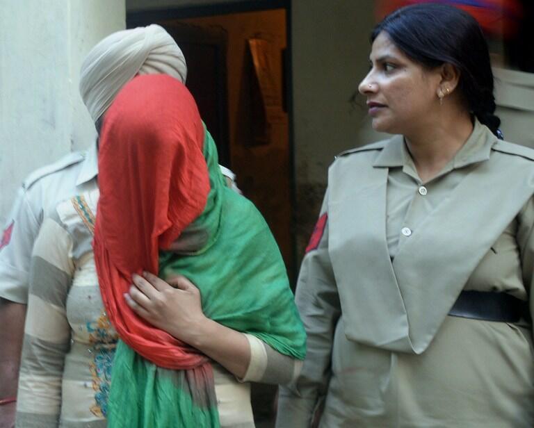La police indienne escorte une infirmière, accusée d'avoir aidé un grand-père à vendre son petit-fils, tout juste né.