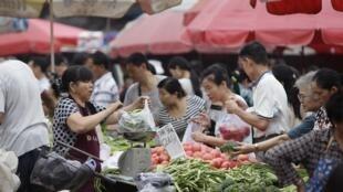 Chineses compram legumes no mercado central de Pequim, em foto do dia 9 de julho.