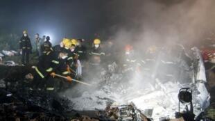 Bomberos trabajan en el lugar del accidente de un avión en China.