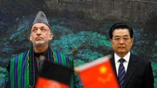 Le président afghan Hamid Karzaï (G) les yeux levés, à côté du président chinois Hu Jintao (D) pendant une cérémonie de signature d'accords au Palais de l'Assemblée du peuple à Beijing, le 24 mars 2010.