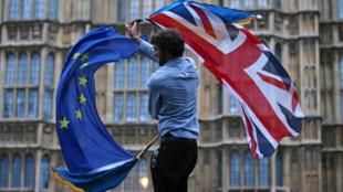 Frente al parlamento británico, un ciudadano con ambas banderas