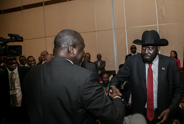 Le président sud-soudanais Salva Kiir (D) serre la main de l'opposant Riek Machar lors d'une rencontre en Ethiopie, le 21 juin 2018.