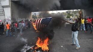 Демонстрант сжигает флаг США на акции протеста в Гаити, Порт-о-Пренс, 15 февраля 2019 г.