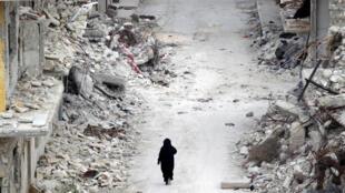 Mulher caminha pelas ruínas na cidade de Maaret al-Numan, província de Idlib.