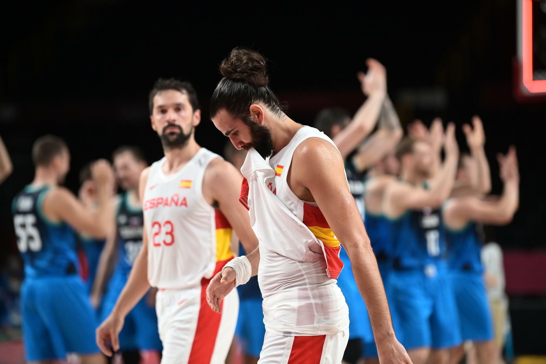 Los españoles Ricky Rubio (en primer término) y Sergi Llull se retiran de la pista mientras los jugadores eslovenos celebran su victoria en el partido del grupo C de los Juegos Olímpicos de Tokio, disputado el 1 de agosto de 2021 en Saitama (Japón)