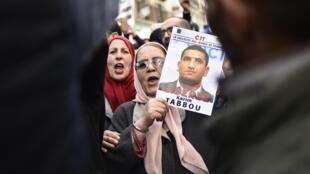 Una manifestante muestra una foto de Karim Tabbou, para quien pide su liberación, el 24 de enero de 2020 en Argel