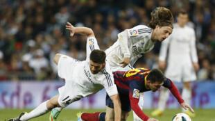 Dan wasan Barcelona, Lionel Messi yana kokarin tsira da kwallo a tsakanin 'Yan Real Madrid Xavi Alonso da Luka Modric a karawar Clasico
