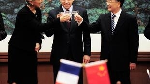 Le chef du gouvernement français François Fillon (c) en compagnie de la ministre de l'Economie Christine Lagarde (g) et du Premier ministre chinois Wen Jiabao, le 21 décembre 2009 à Pékin.