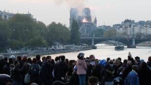 Des touristes assistent à l'embrasement de Notre-Dame de Paris.