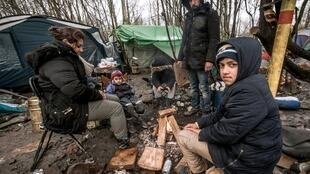 Family members sit around a fire on February 18, 2016 in the refugee and migrant camp in Grande-Synthe near Dunkirk, northern France, where 2,500 refugees from Kurdistan, Iraq and Syria live.