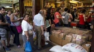 Pessoas fazem fila para comprar mantimentos em uma loja em Atenas, Grécia.