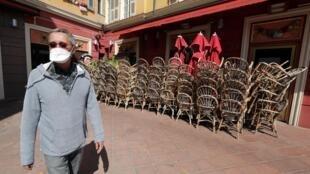 法國尼斯街頭,關閉中咖啡館前一個口罩的路人.