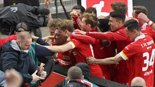 Union Berlin striker Max Kruse (C) is mobbed by team-mates after his winning goal