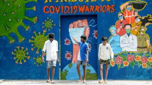 Tres jovenes caminan frente a un mural que rinde homenaje a los trabajadores esenciales durante la pandemia en Chennai, India, el 6 de agosto