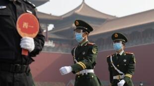 Công an Trung Quốc đeo khẩu trang và kính bảo hộ đi phía bên ngoài Tử Cấm Thành, Bắc Kinh, ngày 01/05/2020.