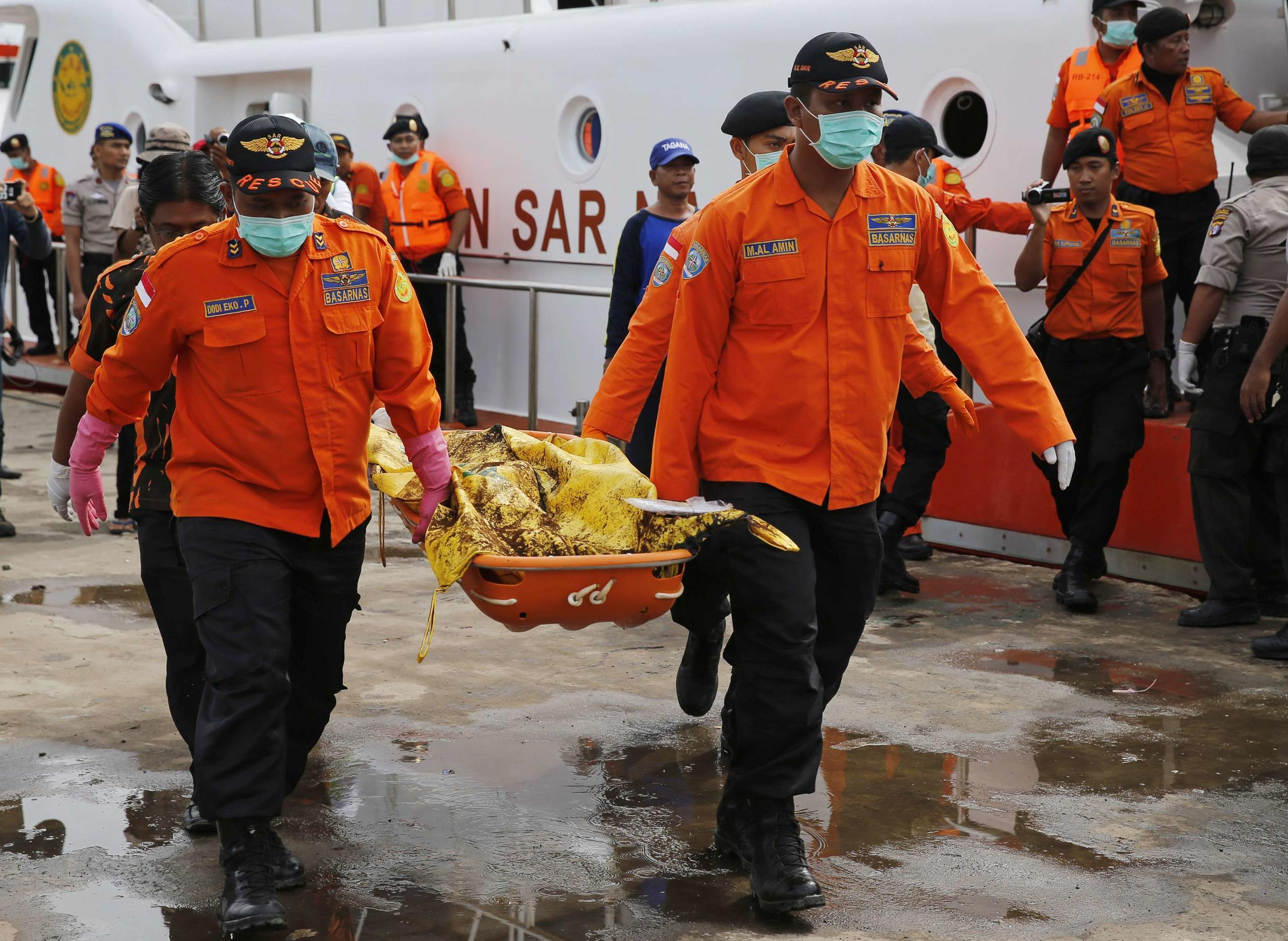 Indonesian rescue workers unload bodies taken from the wreckage of AirAsia flight QZ8501