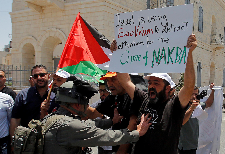 """Manifestante palestiniano segura um cartaz durante um protesto que assinala o 71º aniversário do """"Nakba"""" e contra o Festival Eurovisão da Canção, organizado por Israel, na Cisjordânia ocupada por Israel. 15/05/19"""