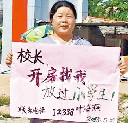 女权活动人士叶海燕举牌在海南万宁第二小学门前抗议该校校长猥亵女童。2013年5月27日。
