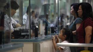 资料图片:香港移民局官员在罗湖桥边境站检查入港的中国大陆人证件。摄于2012年8月24日