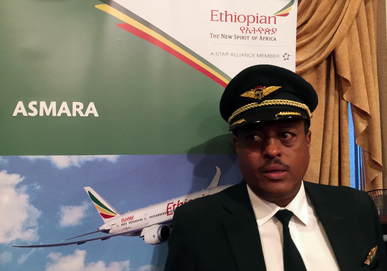 Le capitaine Yoseph Hailu de la compagnie Ethiopian Airlines se tient près d'une affiche publicitaire pour le vol vers Asmara pendant la cérémonie d'inauguration, le 18 juillet 2018, à l'aéroport international de Bole à Addis-Abeba.