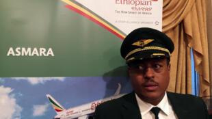 Le capitaine Yoseph Hailu de la compagnie Ethiopian Airlines devant une affiche publicitaire pour le vol vers Asmara pendant la cérémonie d'inauguration, le 18 juillet 2018, à l'aéroport international de Bole à Addis-Abeba.