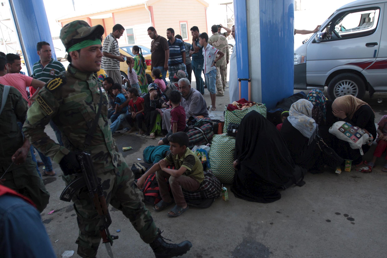 Иракский ополченец-шиит и группа суннитов, переселенных из Рамади, 19 мая 2015 года.