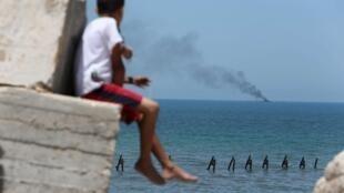 В секторе Газа наблюдают над загоревшимся египетским судном, 16 июля 2015 г.