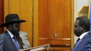 Riek Machar (D) et Salva Kiir (G) lors de la signature de l'accord de paix le 9 mai 2014, à Addis Abeba..