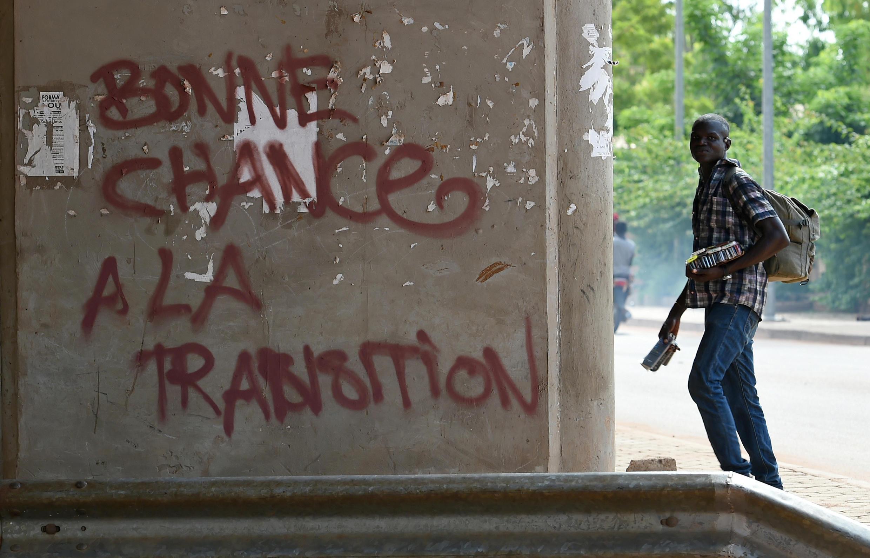 A Ouagadougou, un homme passe devant un graffiti souhaitant bonne chance à la transition qui doit se terminer après les prochaines élections au Burkina Faso.