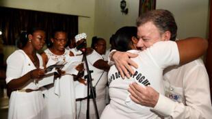 Presidente da Colômbia, Juan Manuel Santos, abraça uma vítima do massacre de Bojayá, ocorrido em 2002.