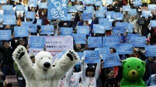 Manifestantes mostram cartazes pedindo proteção ao clima durante marcha em Tóquio neste sábado, 28 de novembro de 2015.
